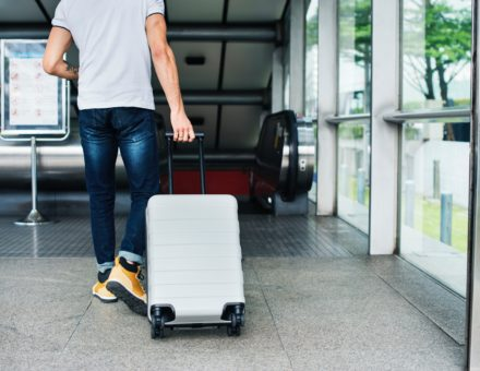man rolling suitcase in the airport