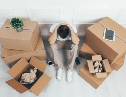 man sitting between cardboard boxes