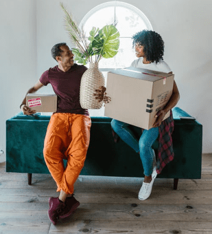 Two people holding moving boxes in a house